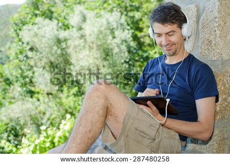 young man holding a tablet with headphones, outdoor - stock photo
