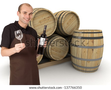 Young man holding a wine bottle and a wineglass, with wine barrels at the background - stock photo