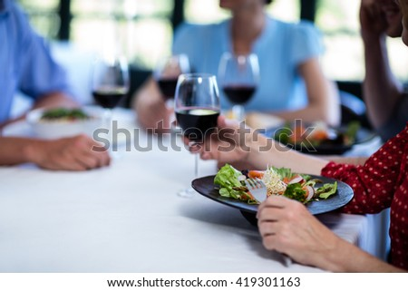 Young man holding a wine glass while having lunch with friends in restaurant