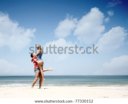 Young man holding a woman and standing on warm sand at sunny day by a sea