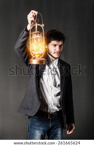 Young man holding an oil lamp in the darkness. - stock photo