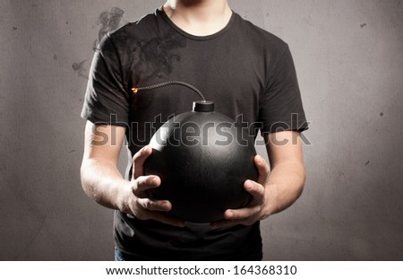 young man holding an old fashioned bomb - stock photo