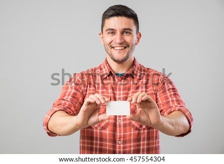 Young man holding and showing blank business card isolated on gray background - stock photo