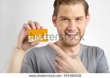 young man holding and showing card