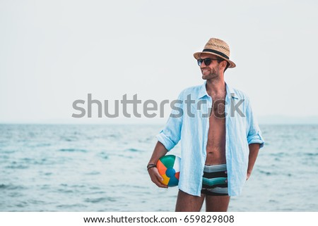 Young man holding ball at the beach