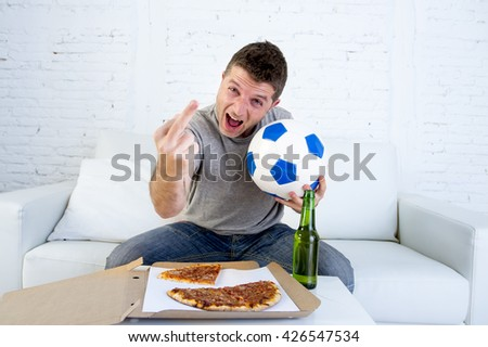 young man holding ball watching football game on television at home sofa couch with pizza box and beer bottle celebrating goal or victory gesturing crazy giving the finger to the opponent team - stock photo