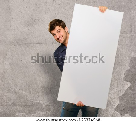 Young Man Holding Banner On Wall - stock photo