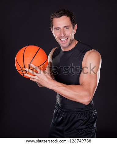 Young Man Holding Basketball Isolated On Black Background - stock photo