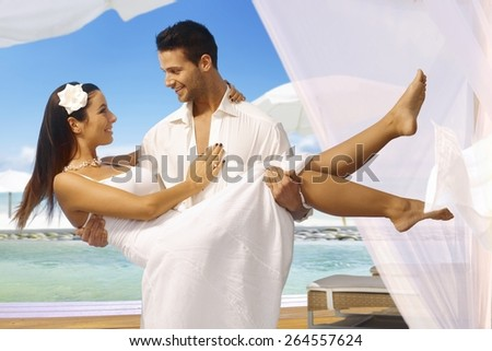 Young man holding beautiful bride in arms after dream wedding on tropical island, both smiling happy. - stock photo