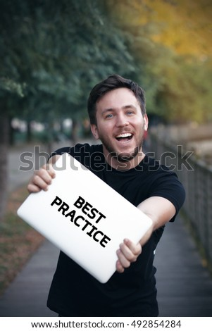 Young man holding Best Practice sign