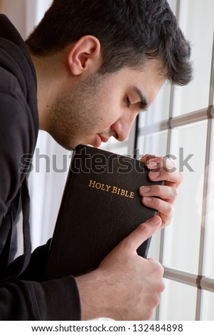 Young man holding Bible and praying by window - stock photo