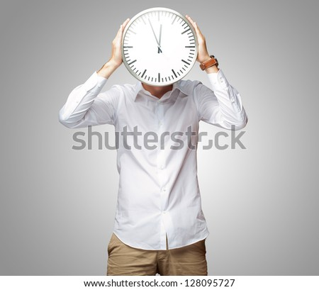 Young Man Holding Big Clock Covering His Face On Gray Background