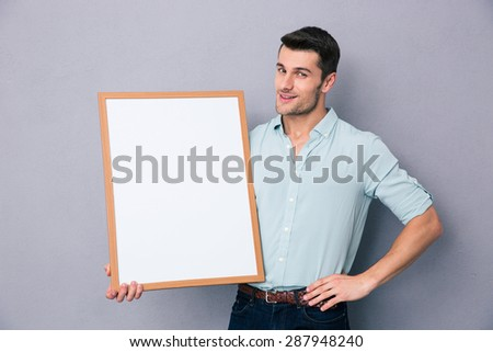 Young man holding blank board over gray background and looking at camera