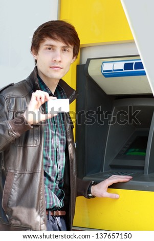 young man holding blank credit or business card going to use atm cash machine - stock photo