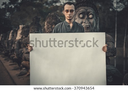 Young man holding blank placard in dark mystic location