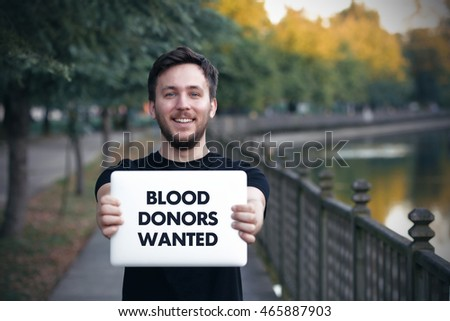 Young man holding  Blood Donors Wanted sign