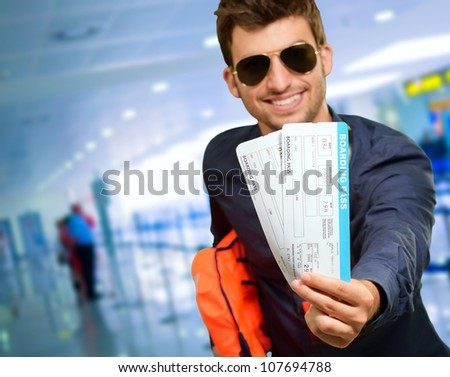 Young Man Holding Boarding Pass, indoor - stock photo