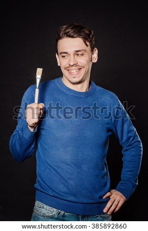 young man holding brush and painting virtual wall.  emotions, facial expressions, feelings, body language, signs. image on a black studio background. - stock photo
