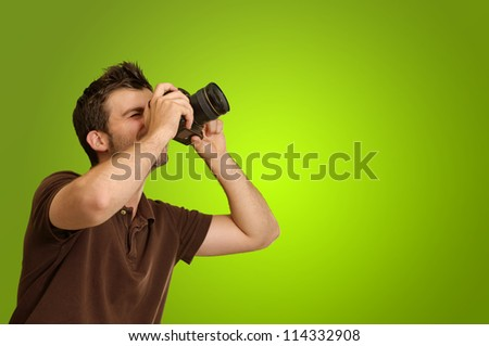 Young Man Holding Camera On Green Background