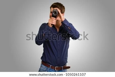 Young Man Holding Camera On Grey Background