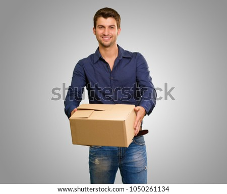 Young Man Holding Cardbox On Grey Background