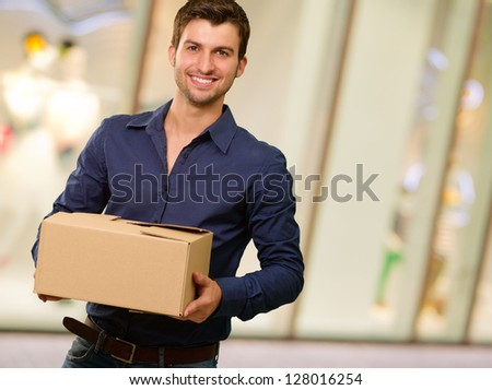 Young Man Holding Cardboxes, Indoors - stock photo