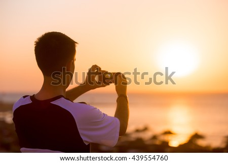 Young man holding cellphone taking photograph in picturesque sea scenery, seashore and beach with sun umbrellas on the background, back view