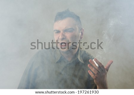 Young man holding cigarette aversion smoking badly. Suffocating. Quit and give up smoking. Space in the cigarette smoke.  smoking kills. Gray background. Studio shot. - stock photo