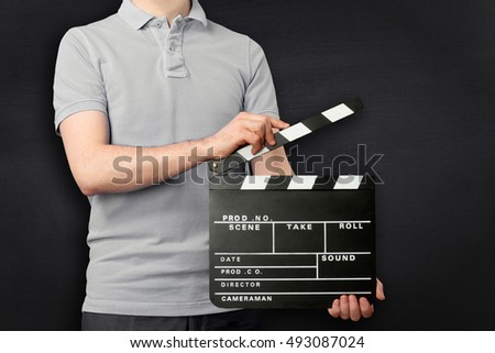 Young man holding clapper board isolated on black background