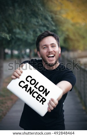 Young man holding Colon Cancer sign