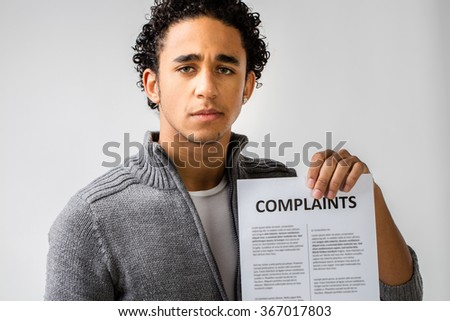 young man holding complaints sheet and maybe he's a customer or at service
