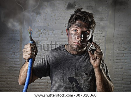 young man holding electrical cable smoking after domestic accident with dirty burnt funny face expression calling desperate with mobile phone asking for help in electricity DIY wrong repairs concept   - stock photo