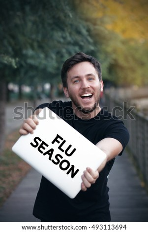 Young man holding Flu Season  sign