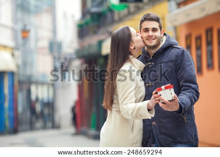 Young man holding gift while being kissed by his girlfriend - stock photo