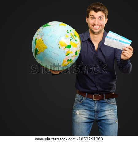 Young Man Holding Globe And Boarding Pass On Black Background