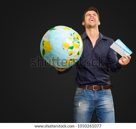 Young Man Holding Globe And Boarding Pass Screaming On Black Background