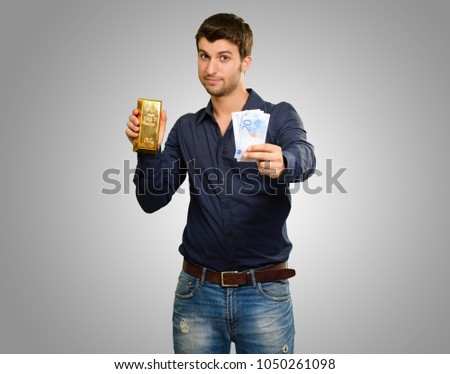 Young Man Holding Gold Bar And Euro Currency On Grey Background