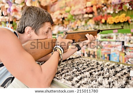 young man holding gun and shooting, playing shooting games while visiting an amusement park  - stock photo