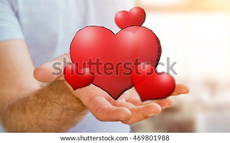 Young man holding hand drawn red heart in his hand on blurred background