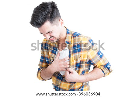 Young man holding hand to his chest during heart attack and palpitations isolated on white background - stock photo