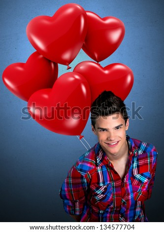 Young man holding heart shaped balloons behind his back - stock photo