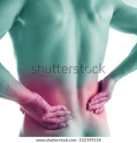Young man holding his back, having pain - stock photo