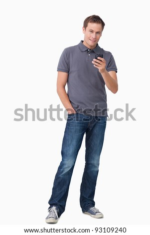 Young man holding his cellphone against a white background - stock photo