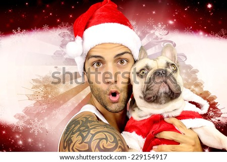Young man holding his french bulldog on a christmas background