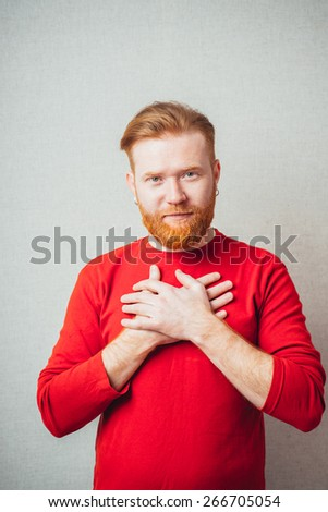 young man holding his hand on his chest - stock photo