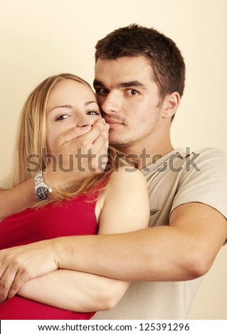 Young man holding his hand over girl's mouth