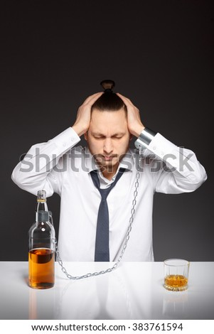 Young man holding his head in despair from the habit to alcohol. Addicted to alcohol, alcoholism concept, social problem - stock photo