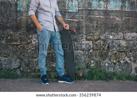 Young man holding his long board