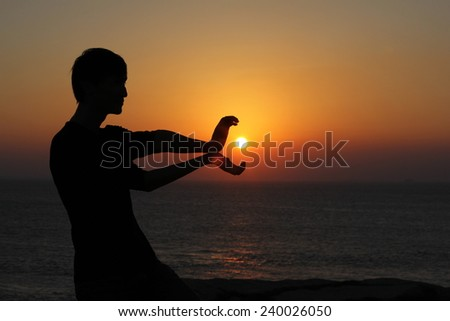 young man holding in hands the setting sun - stock photo