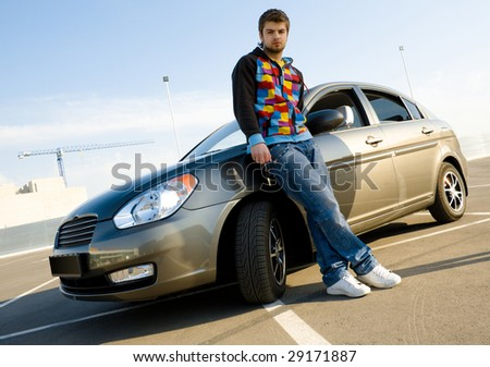 Young man holding keys of his new car - stock photo